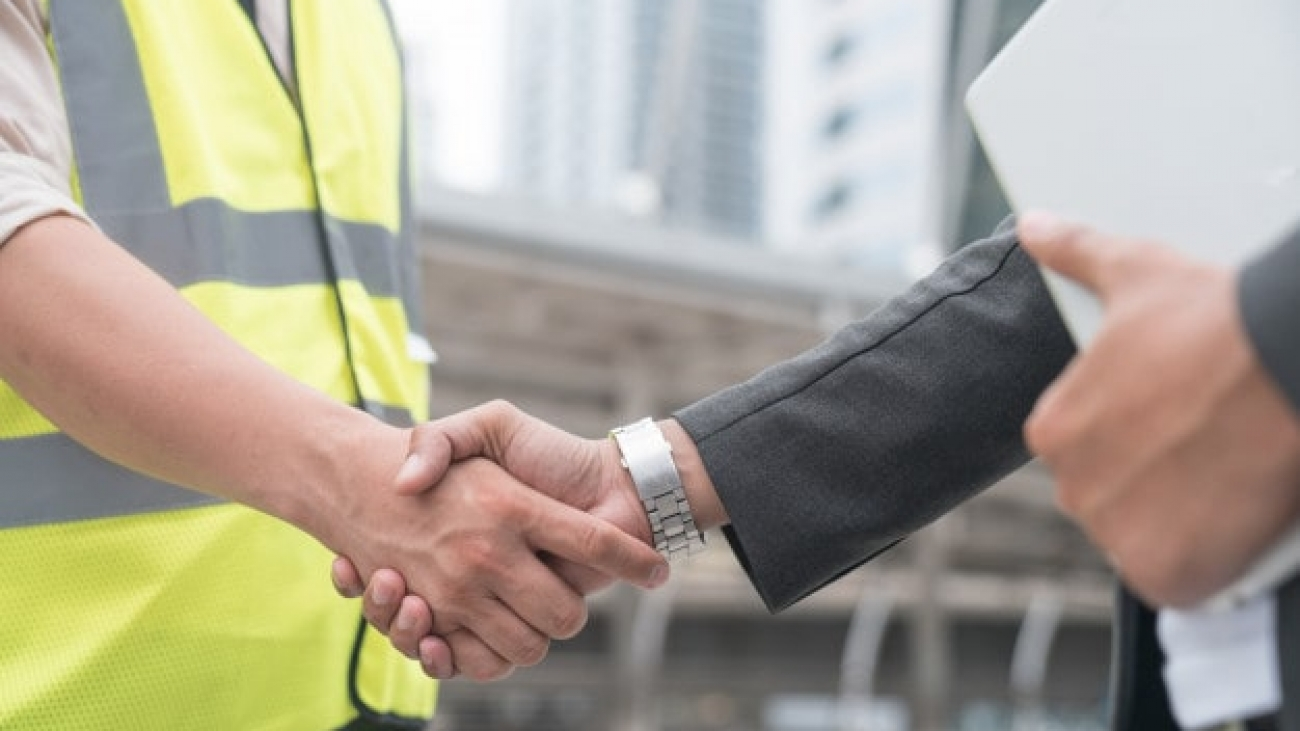 construction-workers-protective-helmets-vests-are-shaking-hands-while-working_35048-1443-min